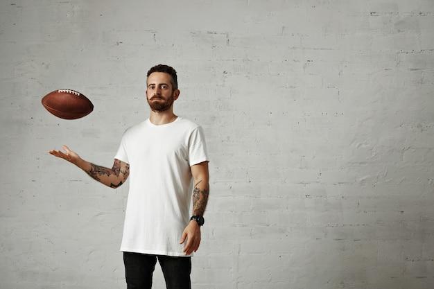 Jonge man gekleed in een blanco wit katoenen mouwloos t-shirt en zwarte spijkerbroek gooien een bruine vintage voetbal geïsoleerd op wit