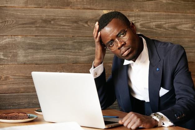 Jonge man gekleed in formeel pak met behulp van laptop