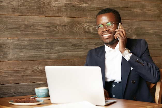 Jonge man gekleed in formeel pak praten aan de telefoon