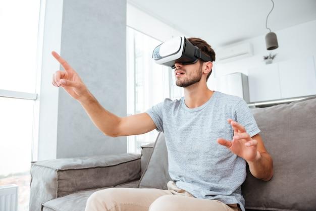 Jonge man gekleed in grijs t-shirt met virtual reality-apparaat zittend op de bank en wijst