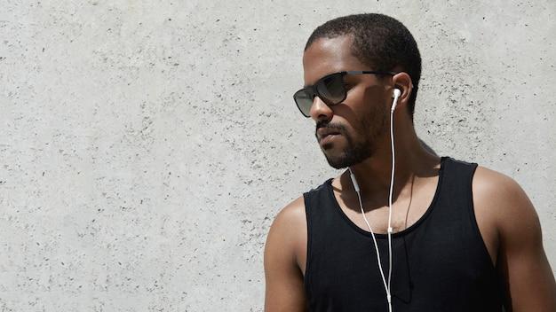 Jonge man gekleed in sportkleding luisteren naar muziek