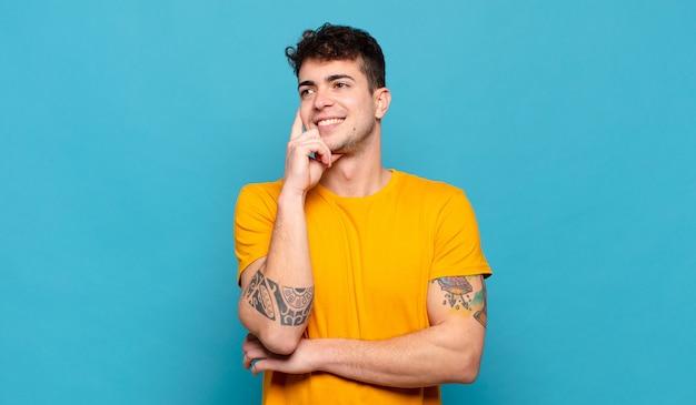 Jonge man gelukkig lachend en dagdromen of twijfelen, op zoek naar de kant