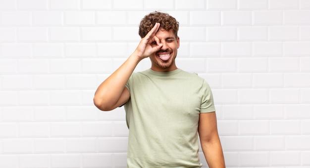 Jonge man gelukkig lachend met grappig gezicht, grappen maken en kijken door kijkgaatje, geheimen bespioneren
