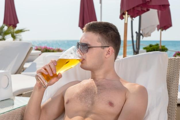 Jonge man geniet van een koud biertje terwijl hij ontspant op een fauteuil in een kustplaats met de oceaan achter hem