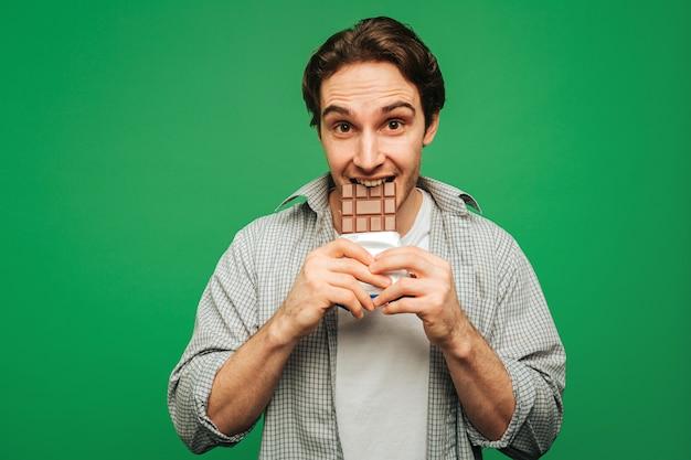 Jonge man geniet van het eten van chocoladereep