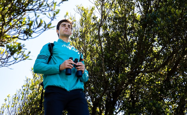 Jonge man geniet van het uitzicht met zijn verrekijker op de top van de berg
