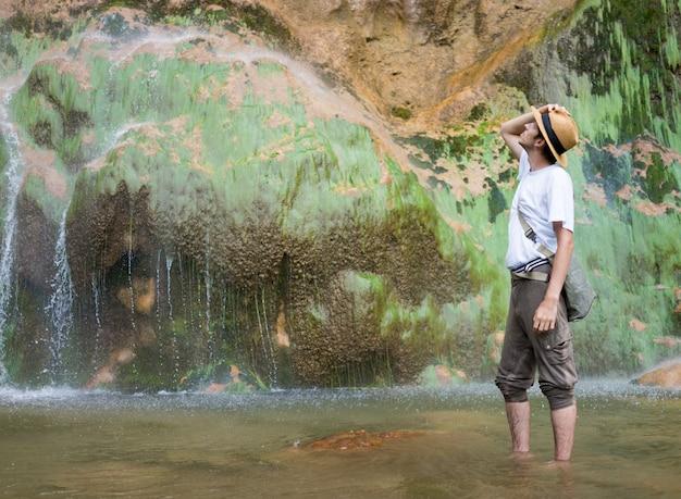 Jonge man genieten in natuurpark aan de voet van grote waterval