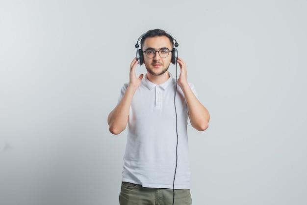 Jonge man genieten van muziek met koptelefoon in wit t-shirt, broek en op zoek zelfverzekerd