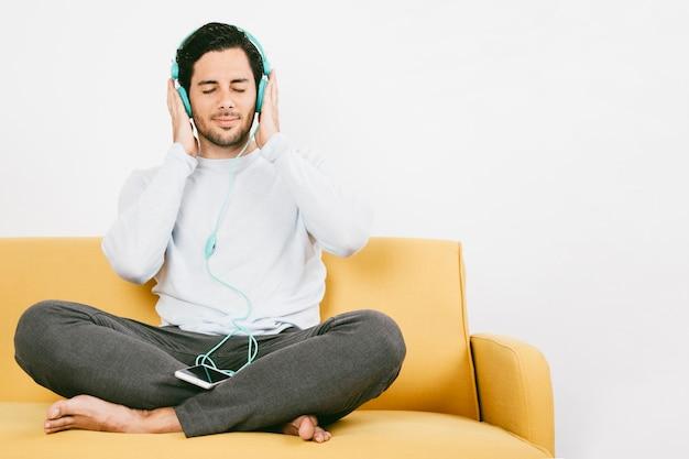 Jonge man genieten van muziek op de bank