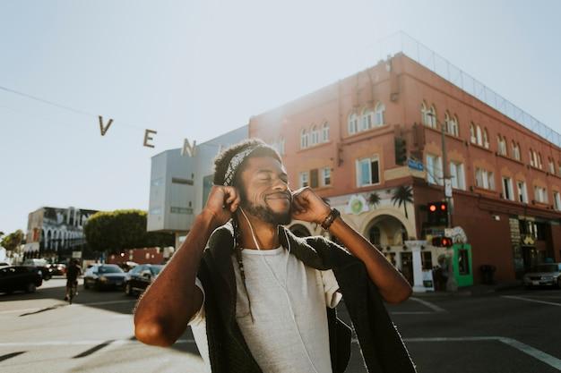 Jonge man genieten van muziek tijdens het wandelen in de straten