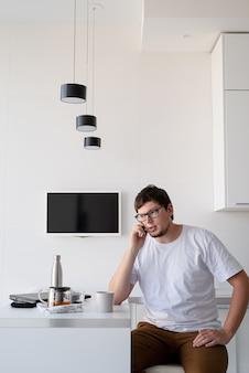 Jonge man genieten van ontbijt thuis, praten aan de telefoon