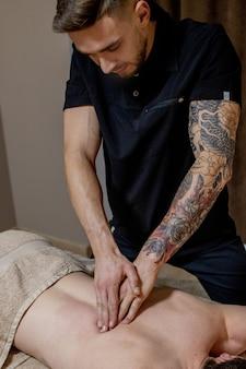 Jonge man genieten van ontspannende lichaamsmassage in spa salon of massageruimte. gekwalificeerde specialist die mannelijke patiënt masseert.