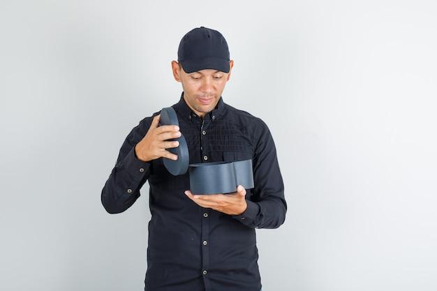 Jonge man geschenkdoos openen in zwart shirt met pet en op zoek verrast