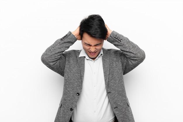 Jonge man gestrest en gefrustreerd gevoel, handen omhoog naar hoofd, moe, ongelukkig en met migraine tegen egale kleur muur gevoel