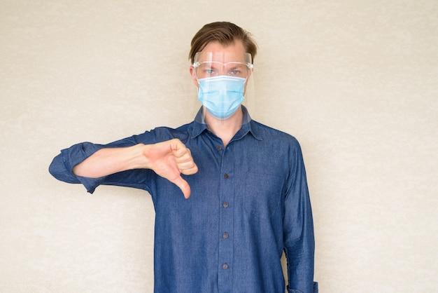 Jonge man geven duimen omlaag met masker en gezichtsscherm op betonnen muur