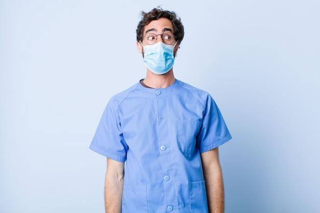Jonge man gevoel geschokt, blij, verbaasd en verrast, op zoek naar de kant met open mond. coronavirus concept