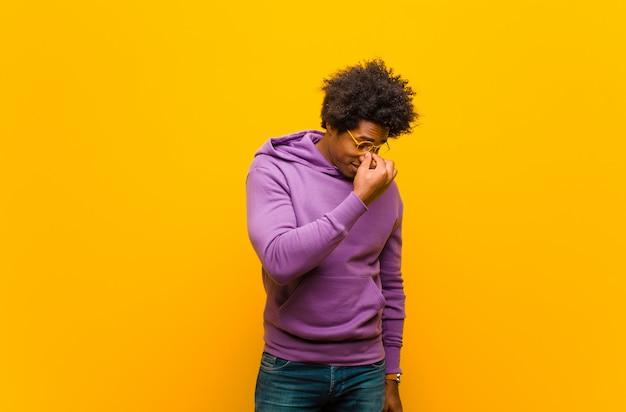Jonge man gevoel gestrest, ongelukkig en gefrustreerd, voorhoofd aanraken en migraine lijden aan ernstige hoofdpijn tegen oranje muur