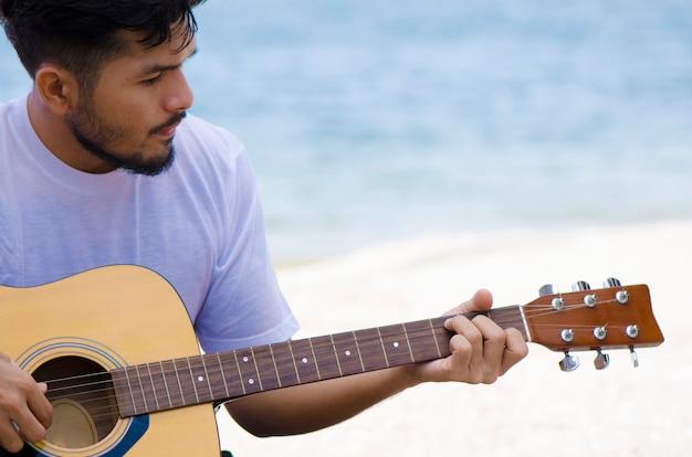 Jonge man gitaar spelen op het strand