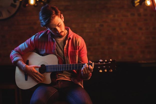 Jonge man gitaarspelen