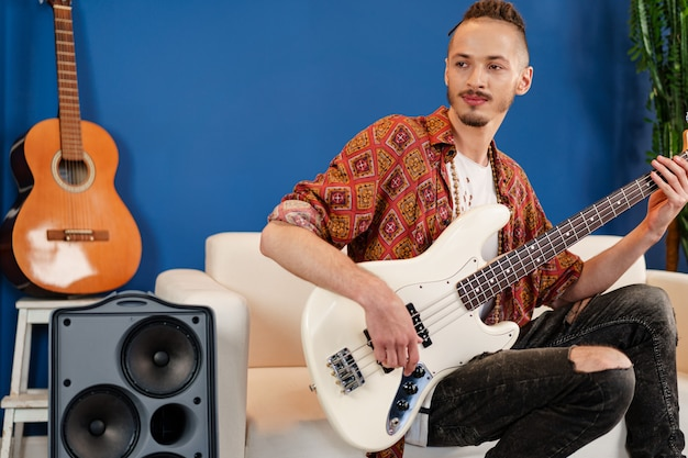 Jonge man gitarist zitten en presteren op een bank