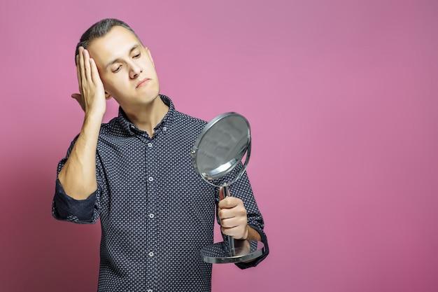 Jonge man gladstrijken voor een spiegel op een roze achtergrond