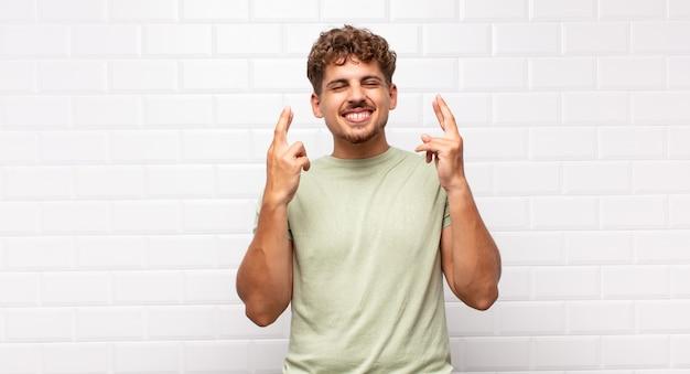 Jonge man glimlachend en angstig beide vingers kruisen, zich zorgen maken en geluk wensen of hopen