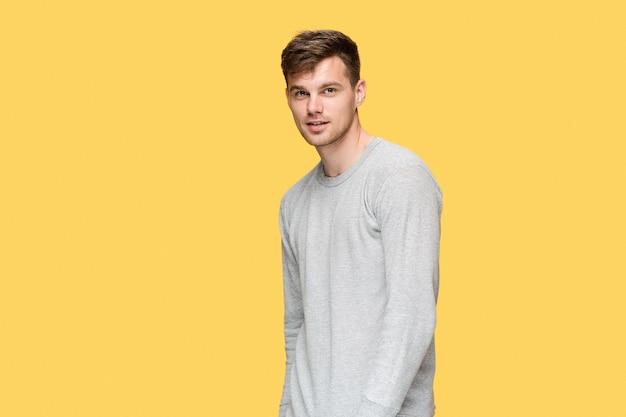 Jonge man glimlachend en camera kijken op gele studio achtergrond