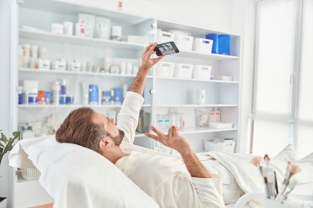 Jonge man glimlachend en selfie maken tijdens het wachten op cosmetische procedure in kliniek voor esthetische cosmetologie.