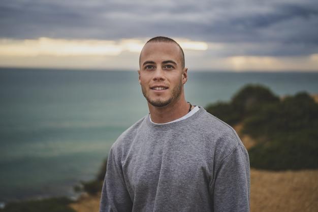 Jonge man glimlachend en staande op een klif in de buurt van de prachtige zee
