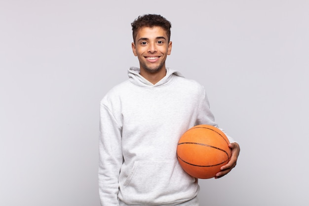 Jonge man glimlachend gelukkig met een hand op de heup en zelfverzekerd, positief, trots en vriendelijke houding. mand concept
