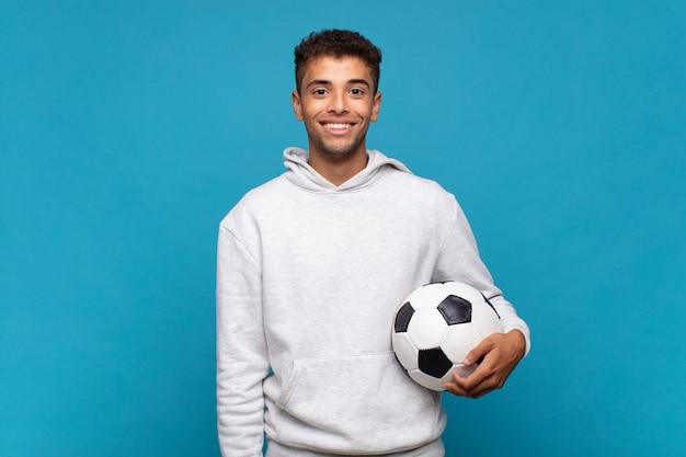 Jonge man glimlachend gelukkig met een hand op de heup en zelfverzekerd, positief, trots en vriendelijke houding. voetbal concept