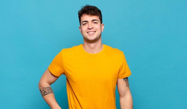Jonge man glimlachend gelukkig met een hand op de heup en zelfverzekerd, positief, trots en vriendelijke houding