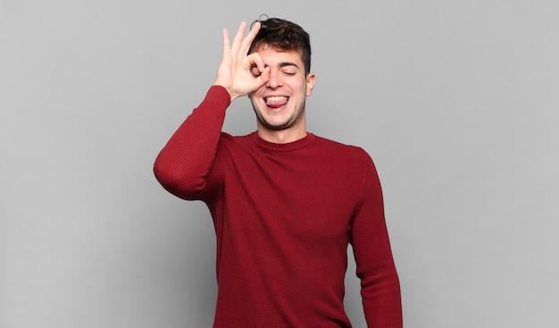 Jonge man glimlachend gelukkig met grappig gezicht, grapje en kijkend door kijkgaatje, geheimen bespioneren