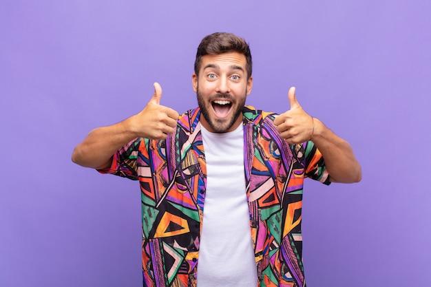 Jonge man glimlachend in grote lijnen op zoek gelukkig, positief, zelfverzekerd en succesvol geïsoleerd
