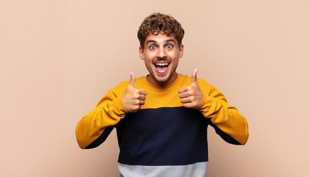 Jonge man glimlachend in grote lijnen op zoek gelukkig, positief, zelfverzekerd geïsoleerd