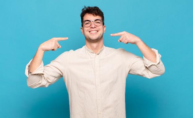 Jonge man glimlachend vol vertrouwen wijzend naar eigen brede glimlach, positieve, ontspannen, tevreden houding