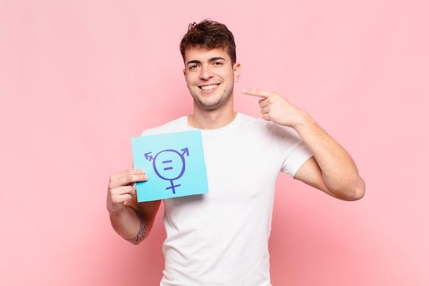 Jonge man glimlachend vol vertrouwen wijzend naar eigen brede glimlach positieve ontspannen tevreden houding