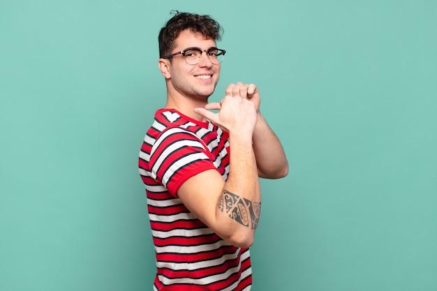 Jonge man glimlachend vrolijk en terloops wijzend naar kopie ruimte aan de zijkant, gelukkig en tevreden gevoel