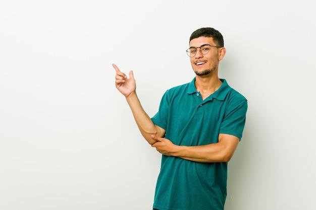 Jonge man glimlachend vrolijk wijzend met wijsvinger weg