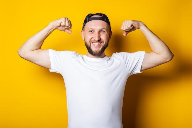 Jonge man glimlacht in een wit t-shirt, sterk, atletisch, toont een biceps. demonstratie van kracht, atletische bouw