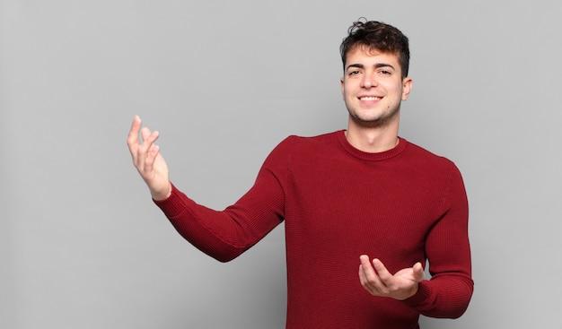 Jonge man glimlacht trots en zelfverzekerd, voelt zich gelukkig en tevreden en toont een concept op kopie ruimte