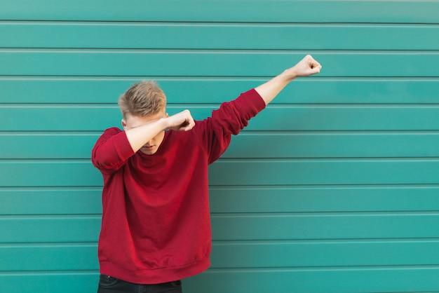 Jonge man gooit schar op turquoise muur