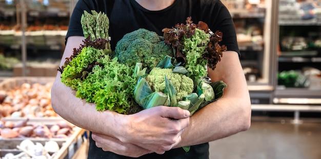 Jonge man groenten kopen op de markt