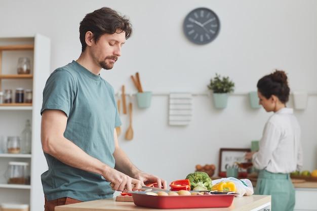 Jonge man groenten snijden voor het diner dat hij zijn vrouw in de keuken thuis helpt