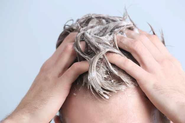 Jonge man haar wassen op kleur achtergrond, close-up