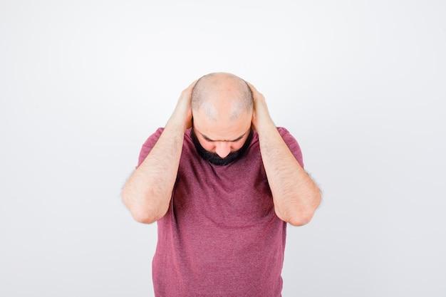 Jonge man hand in hand achter het hoofd terwijl hij naar voren buigt in roze t-shirt en er moe uitziet, vooraanzicht.