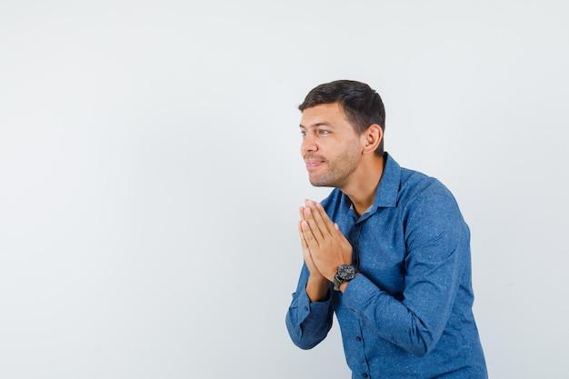 Jonge man hand in hand in biddend gebaar in blauw shirt en ziet er vrolijk uit, vooraanzicht.