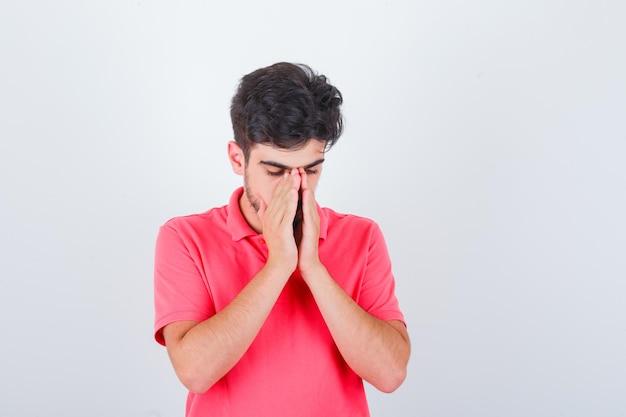 Jonge man hand in hand in biddend gebaar in roze t-shirt en ziet er hoopvol uit, vooraanzicht.
