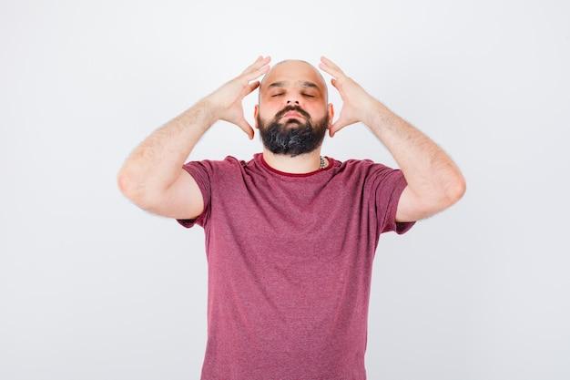 Jonge man hand in hand in de buurt van hoofd in roze t-shirt en ziet er kalm uit. vooraanzicht.