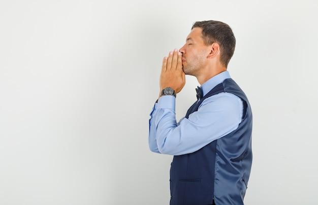 Jonge man hand in hand in gebed gebaar in pak en op zoek hoopvol.